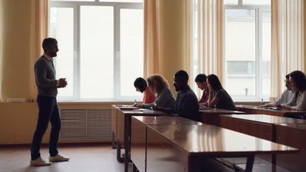 Vousatý muž vysokoškolský učitel je čtení přednášky pro dospělé studenty a gestikuloval, mladí lidé jsou psaní a poslouchá ho. Vysokoškolského vzdělávání a mládež koncepce