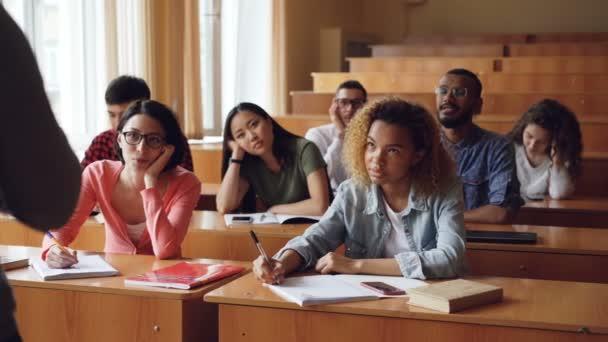 Unavený a znuděný studenti poslouchat učitele a dělala si poznámky v poznámkových blocích sedí u přepážek v univerzitě. Vzdělání, nudy, mladí lidé a učebny koncepce.