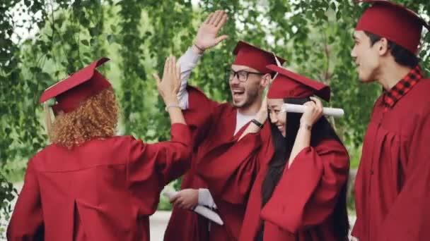 Mnohonárodnostní skupiny studentů, mladých lidí dělají dost na maturitní den nosí tradiční oblečení klobouky a pláště. Koncept milénia, mládí a vzdělání.