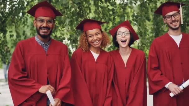 Dolly shot slow motion of laughing young people happy graduates holding diplomas standing in line outdoors on campus enjoying celebration. Graduation day and youth concept.