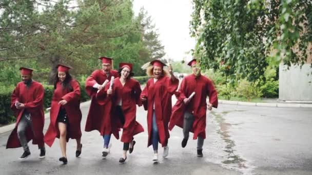 Excited graduating students are running with diplomas on campus territory wearing gowns and traditional hats, it is raining. Higher education and happiness concept.