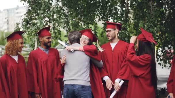 Zpomalený pohyb univerzitní učitel objímala jeho studenty a třásl ruce na závěrečný den s radostí a pýchou. Zelené stromy, budování vzdělávacích institucí je viditelný