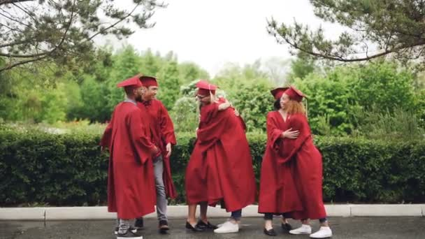 Multiethnic group of friends graduates are hugging, doing high-five and dancing in mortar-boards and gowns traditional graduation clothes. Youth and fun concept.