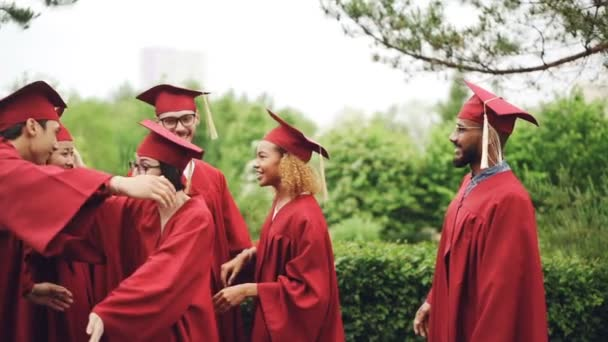 Slow motion of cheerful girls and guys graduating students hugging and shaking hands wearing hats and gowns enjoying graduation day outdoors.