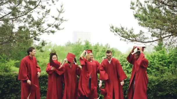 Pomalý pohyb radostné studentů házení mortarboards do vzduchu a je lovit, směje se a těší maturitní den. Vzdělávání, úspěch a moderní mládež koncepce