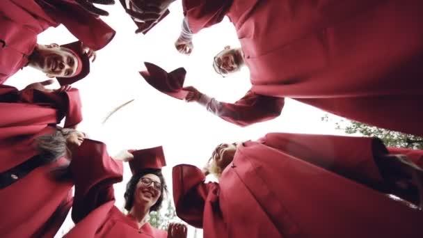 Nízký úhel záběru dívek a kluků Absolventský házení Malty desky na obloze a směje se. Oslavu promoce, tradiční oděvy a koncepce vzdělávání