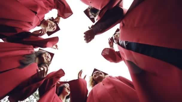 Nízký úhel zpomaleně snímek absolventů stojící v kruhu hází Malty desky na obloze a směje se. Pospolitost, přátelství a koncept moderního životního stylu.