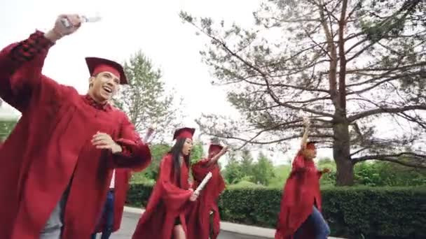 Slow motion of merry and emotional young people running with diplomas wearing mortar-boards and gowns waving scrolls and laughing. Summertime, education and youth concept.