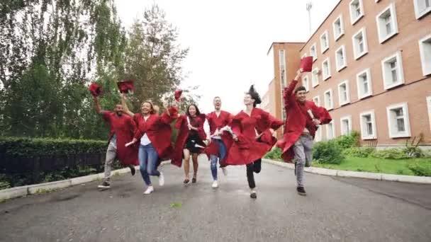 Dolly záběr radostné absolvování studentských s diplomy mává Malty desky a směje se. Vyšší vzdělání, mládež a štěstí koncepce
