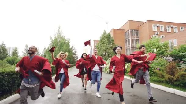Slow motion of merry graduates running, holding diplomas and waving mortarboards enjoying freedom. Higher education, youth and happiness concept.