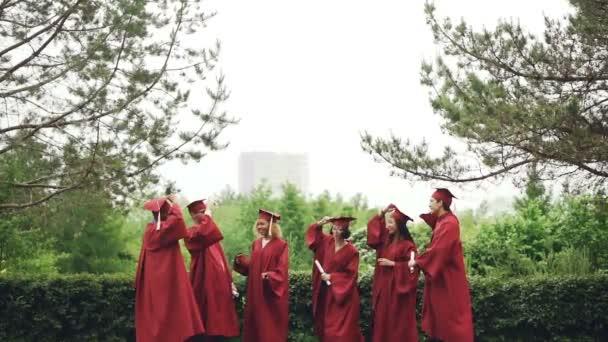 Pomalý pohyb šťastný absolventů sundala slavnostní pokrývka hlavy čepice, házení ve vzduchu, směje se a chytání je pak skákání. Vzdělání, emoce a moderní mládež koncepce