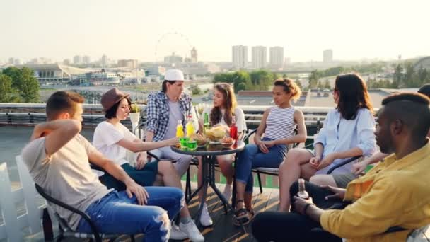 Emotional youth friends are speaking sharing news sitting on rooftop with food and drinks, multi-ethnic group is having fun in summer enjoying conversation and view.