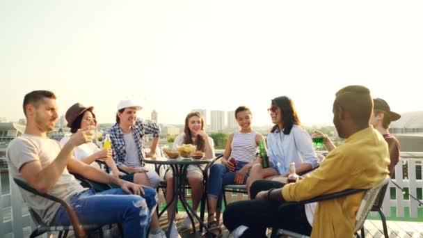 Multiethnic group of friends is talking, toasting then clanging bottles and glasses and drinking beer and soft drinks at table on roof. Beautiful view of city is in background.