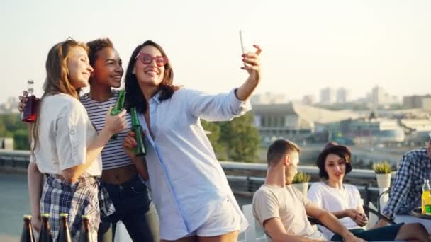 Pretty young ladies are taking selfie with bottles using smartphone during open-air party on roof while their friends are chatting in background. Modern technology and fun concept.