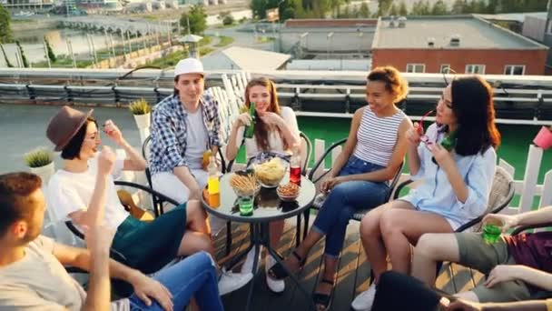 Happy friends are putting hands together then raising them celebrating success sitting at table on rooftop, laughing and talking. Friendship and party concept.
