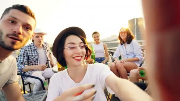 Point of view shot of pretty lady in trendy hat holding camera and taking selfie with friends enjoying rooftop party with soft drinks, people are looking at camera and laughing.