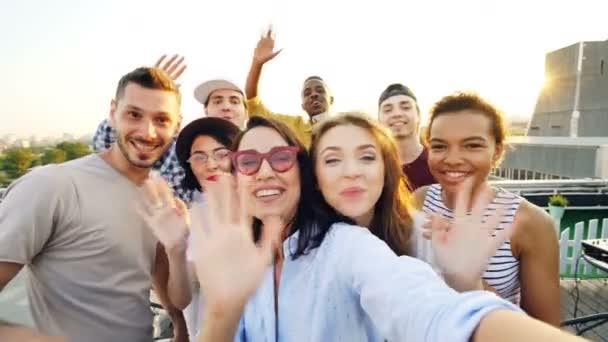 Hlediska záběr mladých lidí video volání, při pohledu na fotoaparát, mluví a se smíchem během party na střeše. Moderní technologie a komunikační koncept.