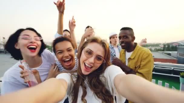 Hlediska záběr mladá dáma blogger nahrávání video pro její blog na střeše večírku tančí a baví se s přáteli. Koncept vlogging, mládež a disco.