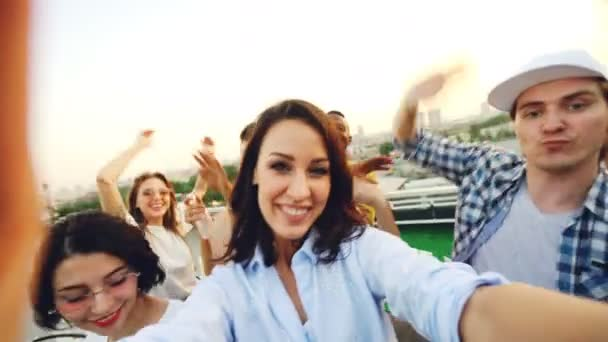 Hlediska záběr mladá žena držící fotoaparát a nahrávání párty s šťastných lidí tančí, smáli se a při pohledu na fotoaparát. Koncept mládeže a zábavy