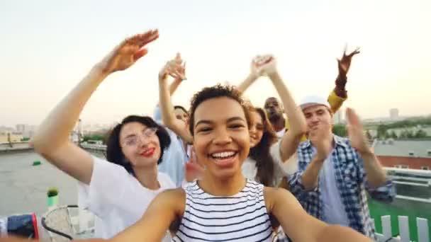 Hlediska záběr americkou afričanku skvěle zábavy při pohledu kamery na střeše party s mnohonárodnostní skupiny přátel. Koncept zábavy a mládež.