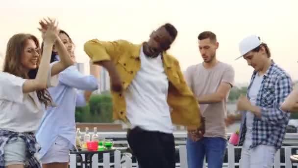Radostné afroamerické muže v trendy oblečení tancuje s mnohonárodnostní skupiny přátel baví na party na střeše v letním dni. Volný čas, radost a přátelství koncepce
