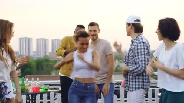 Docela smíšené rasy dívka je s přáteli tancovat a smát těší párty. Zábava, párty venku a koncept moderního životního stylu