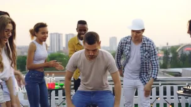 Handsome young man is dancing in circle of friends having fun on rooftop at open-air party. Celebration, active lifestyle and entertainment concept.