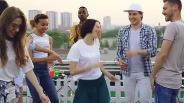 Pretty young woman and her joyful friends are dancing on rooftop celebrating holiday and enjoying good company. Summertime, leisure and hobby concept.