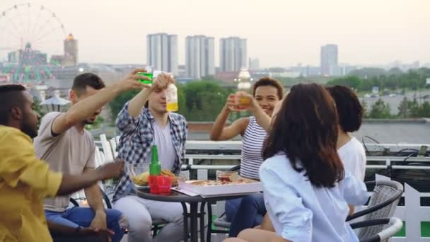 Multiracial group of friends is clinking glasses, drinking soft drinks and eating pizza sitting at table on rooftop celebrating friends reunion. Food and party concept.