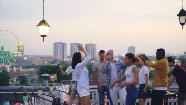 Multiracial group of friends is dancing on rooftop having cool party with DJ in the evening in summer. Joyful youth, entertainment and big city concept.
