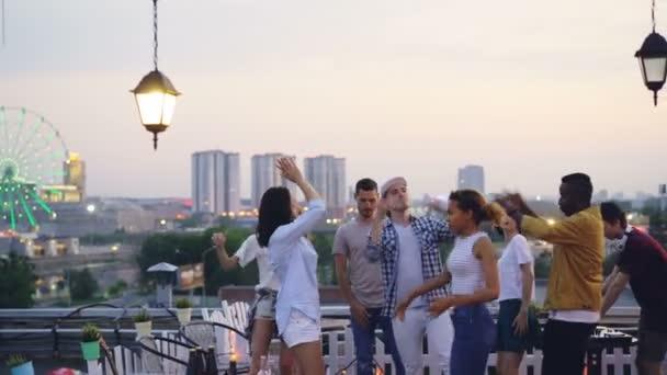 Mnohonárodnostní skupiny přátel se tančí na střeše s cool party s Dj večer v létě. Radostné mládí, zábavy a velkoměsta koncepce
