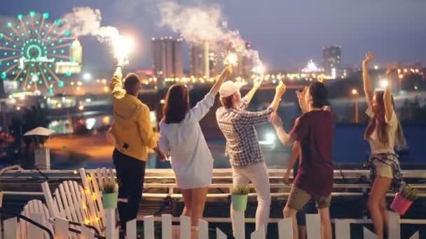 Happy přátelé jsou hořící světla Bengálsko a tanec stojí na střeše slaví svátek společně. Zábavy, přátelství, velkoměsta a radostí koncepce
