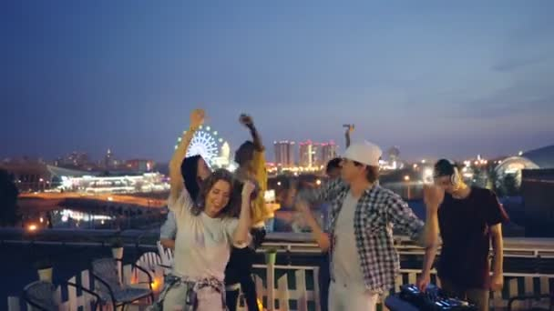 Multiracial group of friends is dancing on rooftop at outdoor party with DJ working with equipment. Modern city nightlife, youth and entertainment concept.