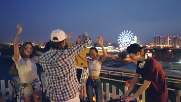 Šťastný muži a ženy tančí s rukou na venkovní party na střeše zatímco Dj je mixování hudby s profesionálním vybavením. Přátelství a párty koncepce