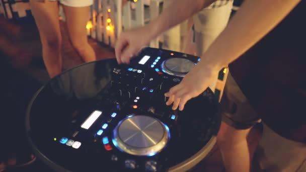 Mani di DJ sono regolazione audio il mixing console creando musica mentre persone stanno ballando intorno a divertirsi. Attrezzature professionali, moderna tecnologia e concetto dei Club.