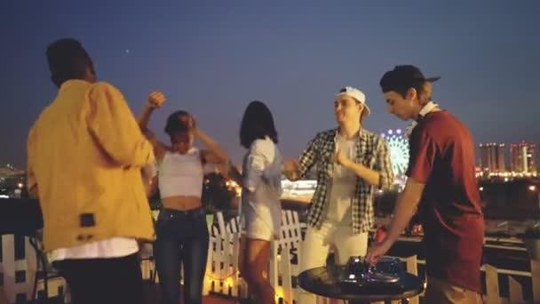 Lächelnde Männer und Frauen tanzen auf Dach Party feiert Urlaub wenn Deejay mit digitalen Mischpult arbeitet. Unterhaltung, Nachtleben und Millennials Konzept