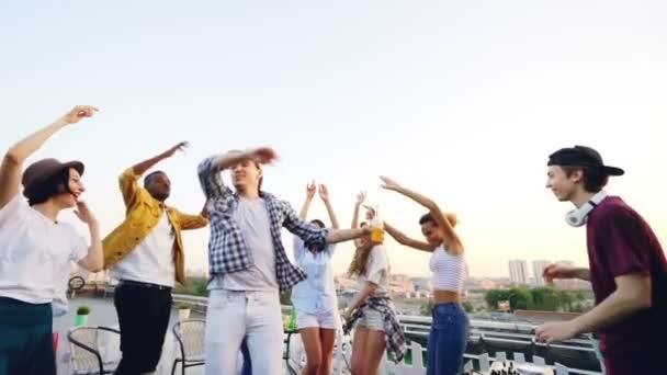 Zpomalený pohyb mladých lidí tančí a směje se přitom samec Dj spolupracuje se zařízením na střeše party v letním dni. Zábavy, mládež a hudební koncept.