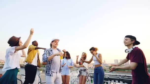 Slow motion of attractive young men and women dancing on roof relaxing and having fun with deejay laughing and using mixing console. Party and friendship concept.