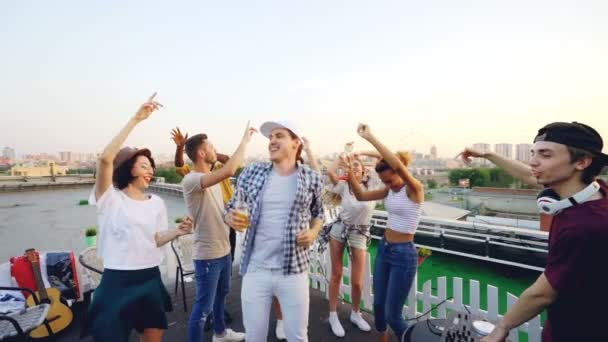 Slow motion of young men and women dancing and laughing when cool DJ is working with mixing console at rooftop party on summer day. Entertainment, youth and music concept.