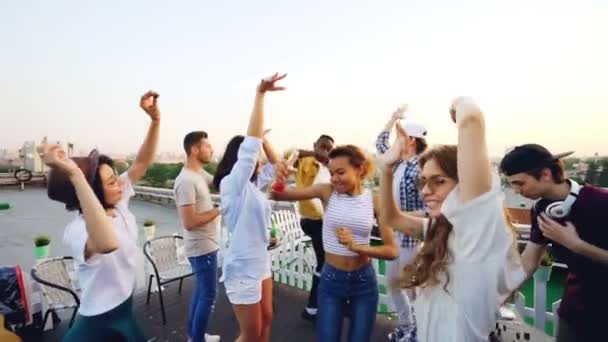 Slow motion of youth dancing on rooftop enjoying party while their friend DJ is mixing music working with equipment wearing headphones. Partying, celebration and fun concept.