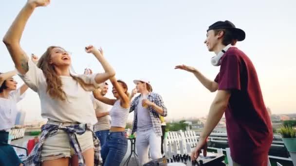 Pomalý pohyb šťastný studentů párty na střeše tanec a smích držení nápoje, zatímco Dj music mixer. Koncepce mládeže, zábava a volný čas