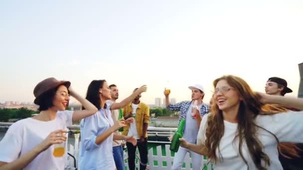 Zpomalený pohyb vzrušený přátel tančí s nápoje pak cinkání lahví a pití na venkovní party na střeše s deejay pomocí zařízení na mix hudby