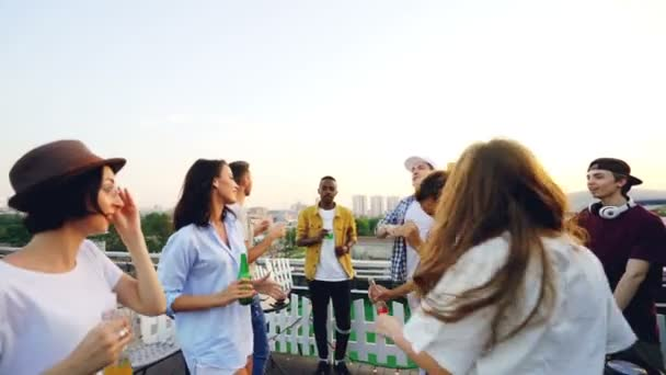 Joyful young people are clanging bottles at modern outdoor party on roof and dancing while professional DJ is working with mixing console. Holidays and summer concept.