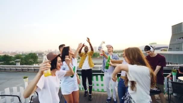 Pomalý pohyb atraktivní dívky a kluci tančí holdingové láhve během party na střeše s Dj pomocí elektronického zařízení. Krásné město je vidět v pozadí