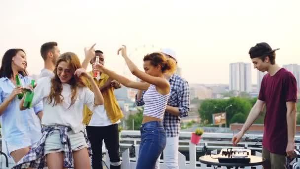 Zpomalený pohyb smát mladých mužů a žen párty na střeše tance a hospodářství lahvové nápoje, když Dj používá profesionální zařízení muzicírování.