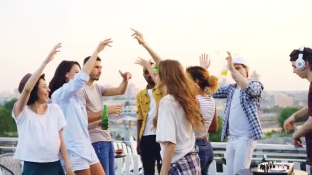 Slow motion of friends dancing with raised hands enjoying music rhythm and laughing while deejay is working with mixing console. Rooftop party, modern lifestyle and youth concept.