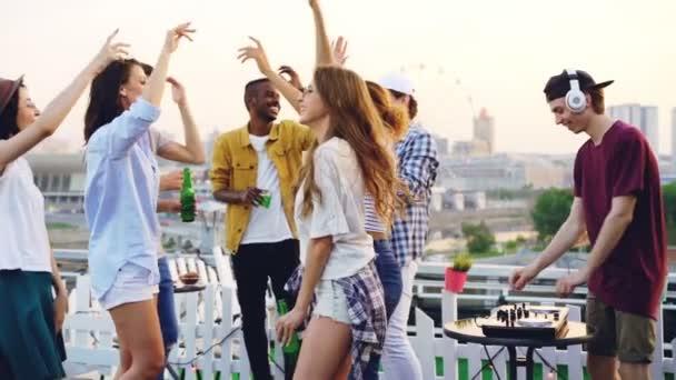 Zpomalený pohyb pohledný mladý muž Dj spolupracuje s profesionálním vybavením a nosit bezdrátová sluchátka na střeše party s šťastných lidí tančí kolem.