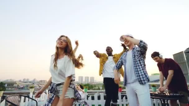 Pomalý pohyb multi-etnické skupiny přátel, tanec a relaxaci pod širým nebem party s Dj pomocí profesionální zařízení. Krásné město je vidět v pozadí