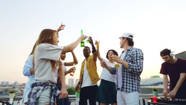 Slow motion of celebration on rooftop with friends dancing and clanging bottles enjoying music and DJ in headphones using mixing console. Beautiful view of city in background.