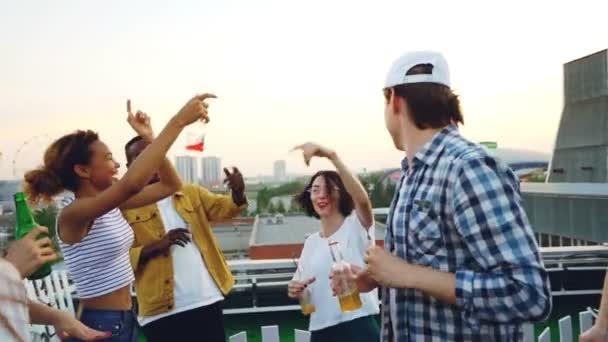 Pomalý pohyb mladých lidí na střeše s nápoji tanec a cinkání lahví slaví svátek. Krásné pohledy z metropole je v pozadí.